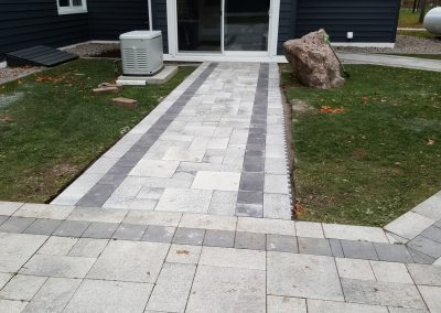 Mosaic grey patio stone with accent border creates an attractive backyard space